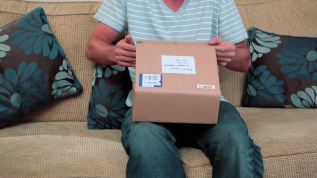 young man opening parcel containing book - förpackning bildbanksvideor och videomaterial från bakom kulisserna