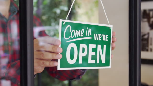 slow-mo: young man opening the shop - shop sign stock videos & royalty-free footage