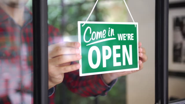 young man opening the shop - open sign stock videos & royalty-free footage
