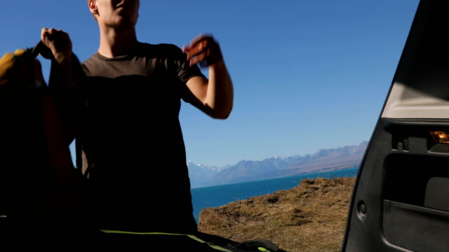 young man opens back of vehicle to reveal view across lake at mt cook - zaino da montagna video stock e b–roll
