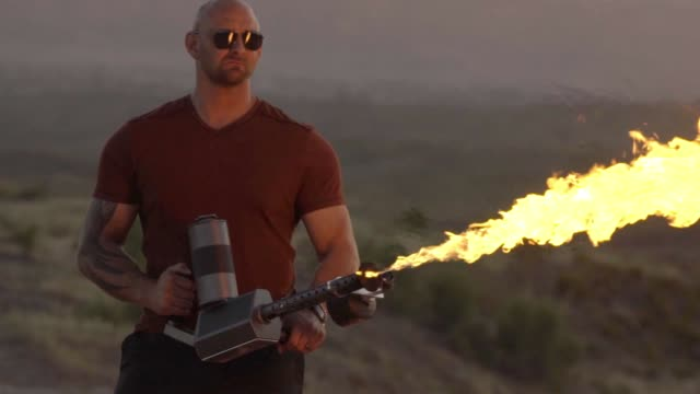 vídeos de stock e filmes b-roll de young man operating a flame thrower in the desert - authority