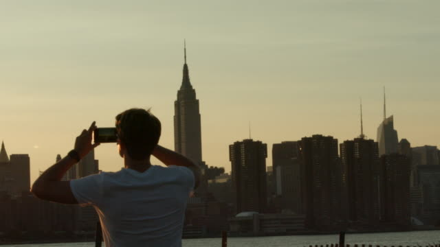 A young man outside taking a picture of the sunsetting along the New York City skyline in slow motion
