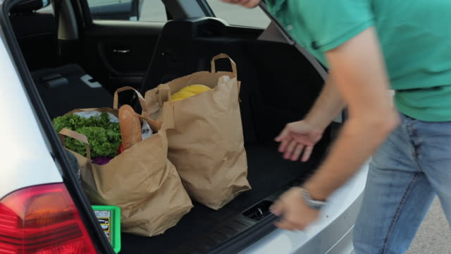 young man packing groceries in car trunk - paper bag stock videos & royalty-free footage