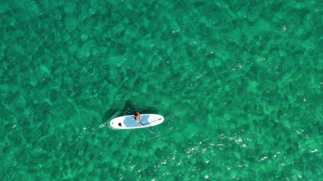young man paddleboarding - greece stock videos & royalty-free footage