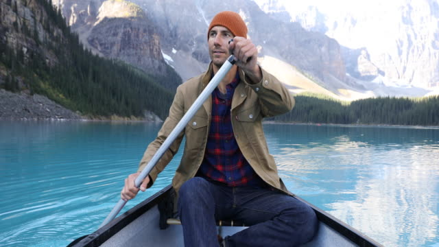 a young man paddling a canoe across the turquoise blue waters of moraine lake. - rudern stock-videos und b-roll-filmmaterial