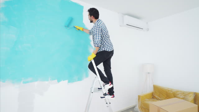 young man painting at home. - ladder stock videos & royalty-free footage