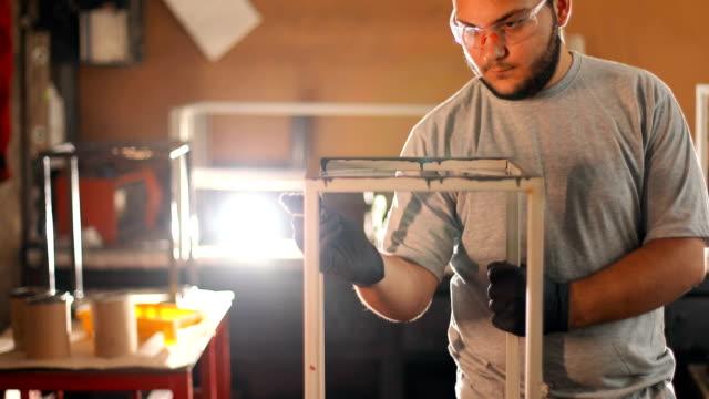 stockvideo's en b-roll-footage met jonge man schilderij in zijn atelier - carving craft product