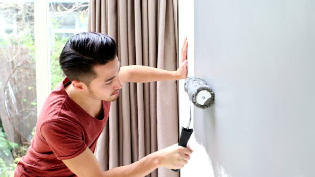 Young man painting wall with paint roller