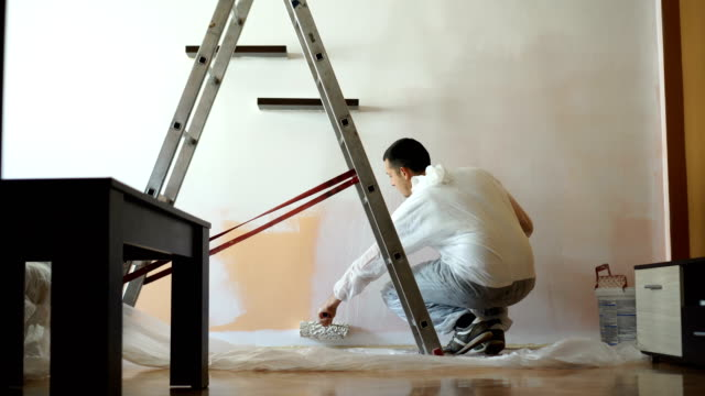 young man paints the wall - wall building feature stock videos & royalty-free footage