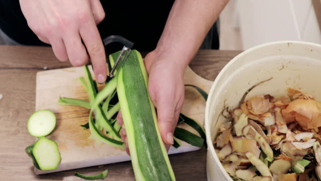 stockvideo's en b-roll-footage met jonge man die courgette peeling en peelings in organisch afvalemmer zet voor compostering-stock video - schil