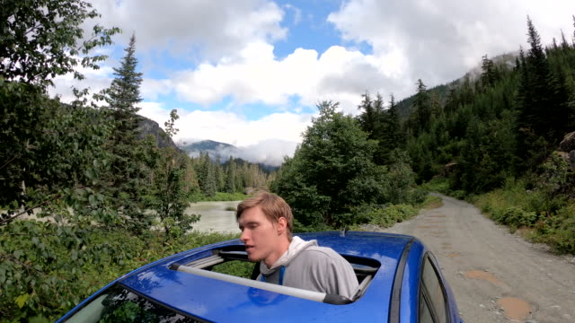 young man peers out through car's sunroof, on mountain road - sun roof stock videos & royalty-free footage
