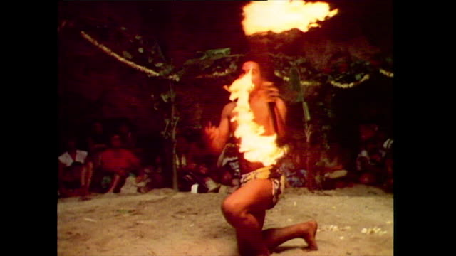 a young man performs a traditional tongan fire dance for tourists passing a flaming baton under his leg and around his neck 1985 - polynesian ethnicity stock videos & royalty-free footage