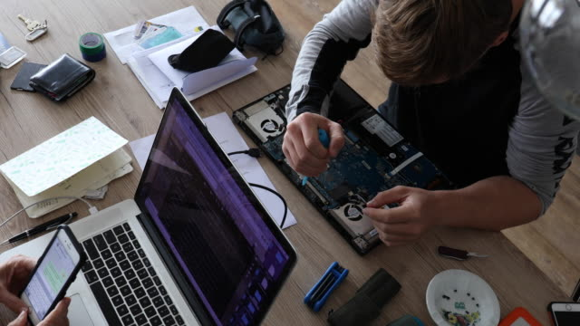 Young man performs computer repairs, indoor setting