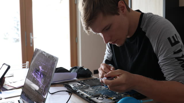 young man performs computer repairs, indoor setting - attitudine video stock e b–roll