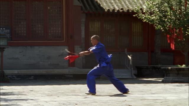 a young man performs kalarippayattu with a sword.\n - sword stock videos & royalty-free footage