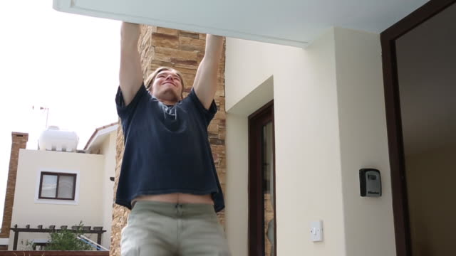 young man performs pull ups, above home door - pull ups stock videos & royalty-free footage