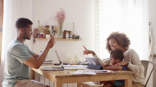 vídeos de stock, filmes e b-roll de homem novo que fotografa a mulher e o filho na cozinha - dois genitores