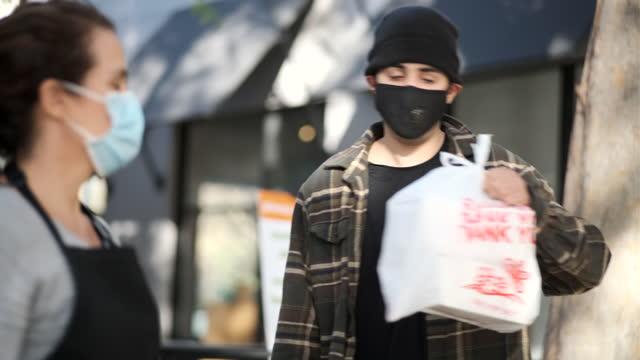 vidéos et rushes de jeune homme ramassant son repas à un ramassage de trottoir - repas à emporter