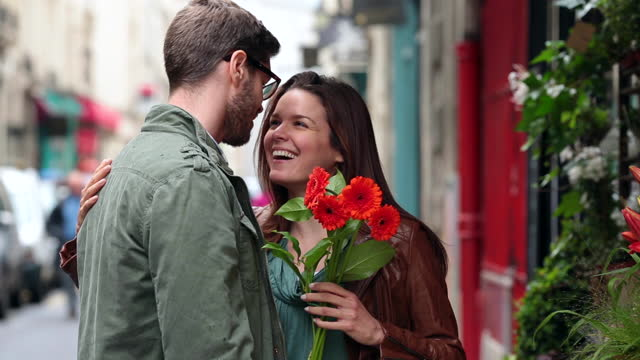 stockvideo's en b-roll-footage met young man picks out flowers for his girlfriend at a sidewalk flower shop in paris. - charmant