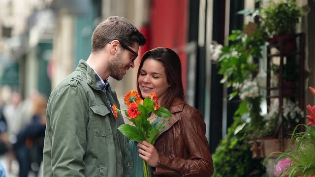 A young man offers his girlfriend flowers.