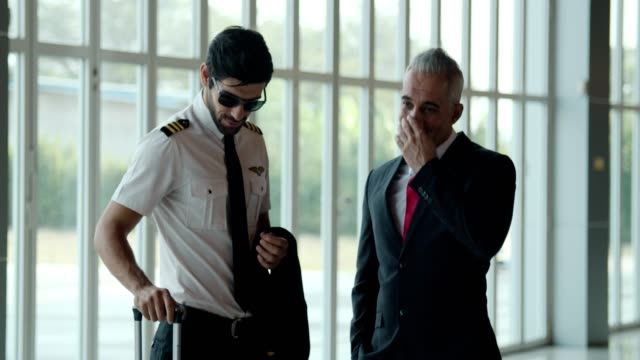 vídeos y material grabado en eventos de stock de joven piloto hablando con un hombre de negocios senior - otros temas