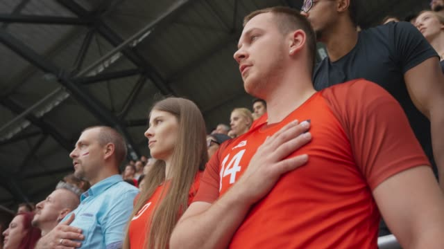 vídeos y material grabado en eventos de stock de young man placing his hand on the heart while the anthem is being played at the stadium - camiseta