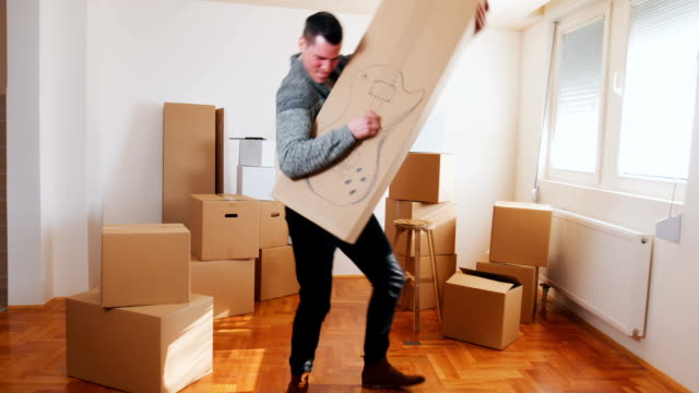 young man play a guitar on a box - moving house stock videos & royalty-free footage