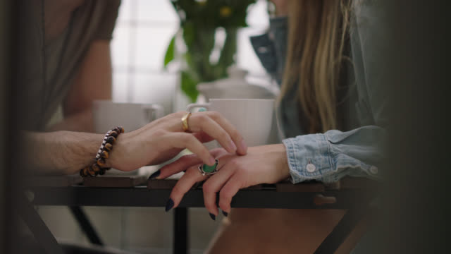 young man playfully walks his fingers across table and caresses his lover's hand. - svinga bildbanksvideor och videomaterial från bakom kulisserna