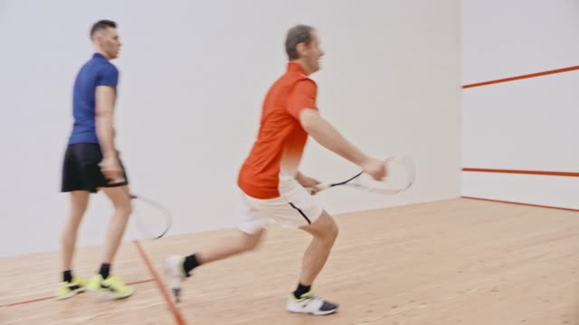 Young man playing a game of squash with his dad
