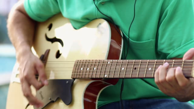 young man playing a guitar - plucking an instrument stock videos and b-roll footage
