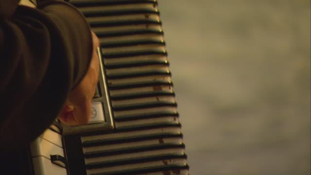 vídeos y material grabado en eventos de stock de cu td tu r/f young man playing accordion by river / basel, switzerland - acordeonista