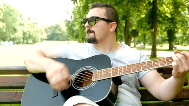 vídeos de stock, filmes e b-roll de jovem tocando guitarra acústica no parque - evento de artes performáticas