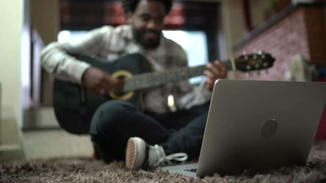 vídeos y material grabado en eventos de stock de joven tocando la guitarra acustic frente a su portátil en casa - evento virtual
