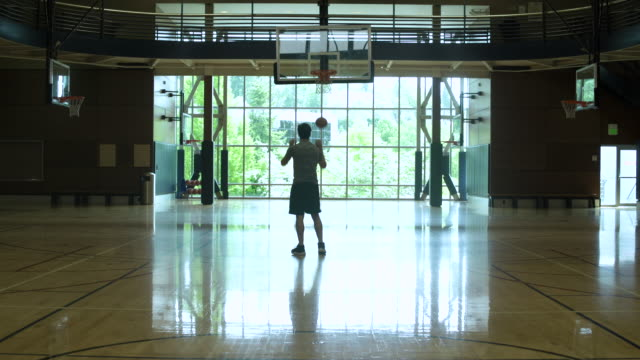 Young man playing basketball by himself