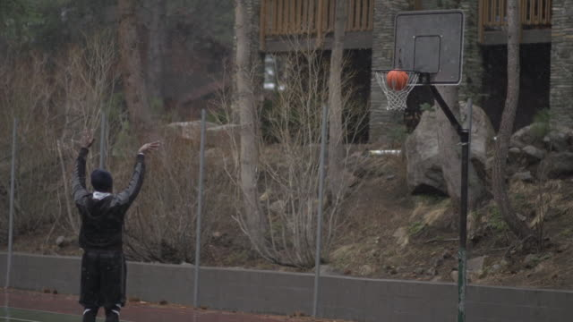 A young man playing basketball in heavy snow fall.