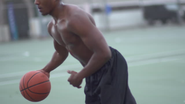 vídeos y material grabado en eventos de stock de a young man playing basketball on a rainy day.  - slow motion - filmed at 240 fps - sólo hombres jóvenes