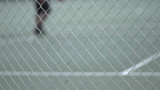 stockvideo's en b-roll-footage met a young man playing basketball on a rainy day.  - slow motion - filmed at 240 fps - infaden