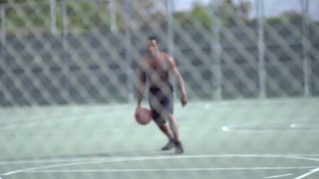 a young man playing basketball on a rainy day.  - slow motion - filmed at 240 fps - solo uomini giovani video stock e b–roll