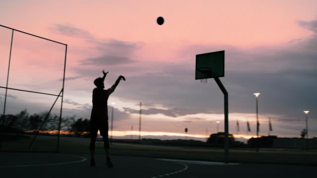 ws ung man spelar basket på utomhus basketplan i skymningen - basketboll boll bildbanksvideor och videomaterial från bakom kulisserna