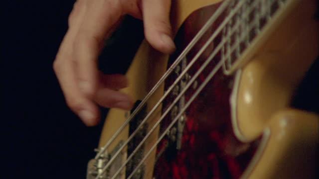 CU, Young man playing electric bass guitar, close-up of hand, Chateau du Parc, Saint Ferme, France