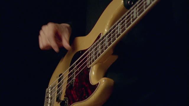 CU, Young man playing electric bass guitar, close-up of hands, Chateau du Parc, Saint Ferme, France