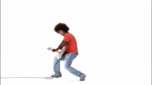 vidéos et rushes de ws, young man playing electric guitar, studio shot - se mordre les lèvres