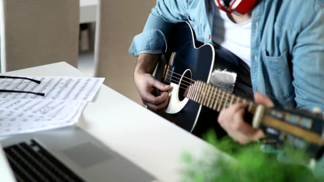 young man playing guitar at home - guitar stock videos & royalty-free footage