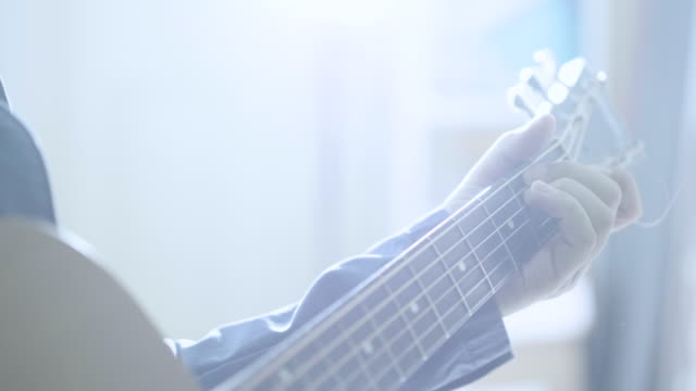 young man playing guitar at home - acoustic guitar stock videos and b-roll footage