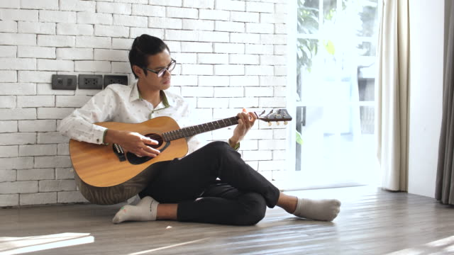 junger mann spielen gitarre zu hause - griffbrett stock-videos und b-roll-filmmaterial