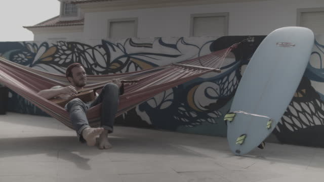 Young man playing guitar in hammock in front of painted wall by a pool at surf camp