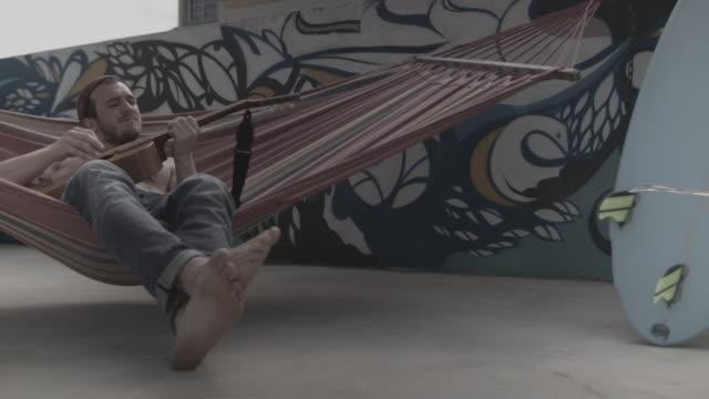 vídeos y material grabado en eventos de stock de young man playing guitar in hammock in front of painted wall by a pool at surf camp - accesorio de cabeza
