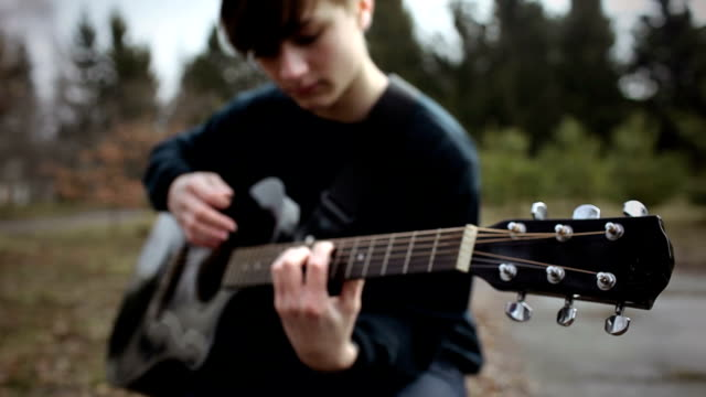 young man playing guitar in park - teenage boys stock videos & royalty-free footage