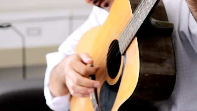 Young man playing guitar indoors.HD format.