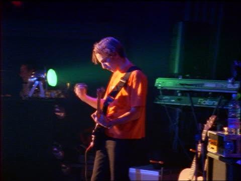 SLIGHT PAN young man playing guitar + man playing keyboard on stage